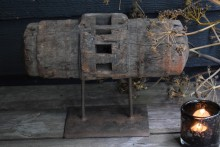 Oud houten wiel as op statief